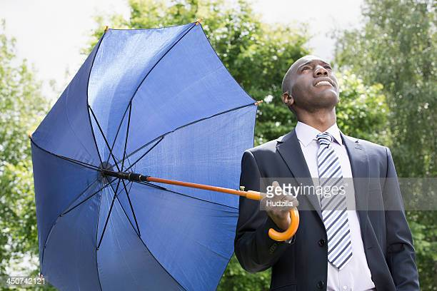 Businessman holding umbrella realising the rain has stopped