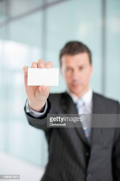 Businessman holding up blank business card