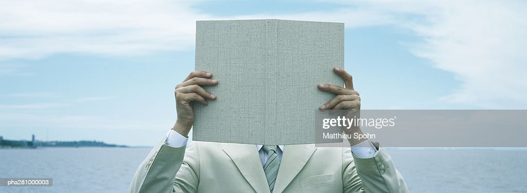 Businessman holding up book in front of face, front view, panoramic : Stockfoto