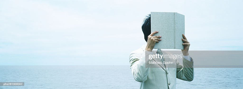 Businessman holding up book in front of face, panoramic : Stockfoto