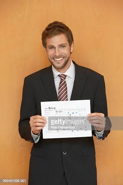 Businessman holding up chart smiling, portrait