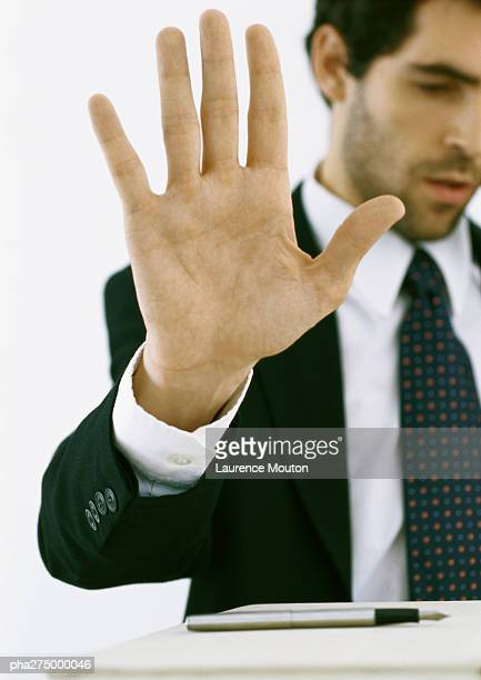 Businessman holding up hand and looking down