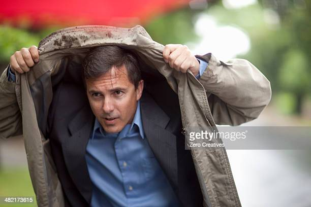 Businessman holding up raincoat to shelter from rain