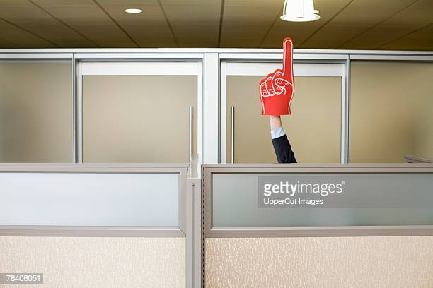 businessman holding up sports foam finger - foam finger stock photos and pictures