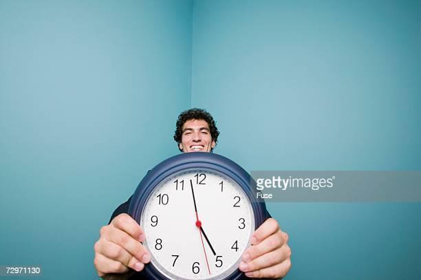 Businessman holding wall clock