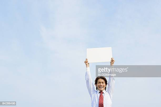 Businessman holding white board against blue sky