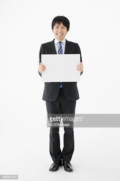 Businessman holding white board, studio shot