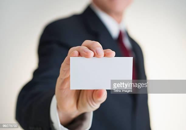 Businessman holding white card