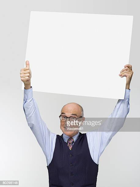 Businessman holding white cardboard, portrait, close-up