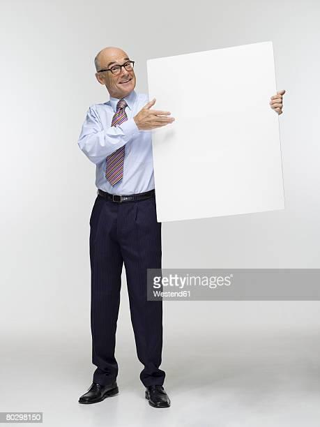 Businessman holding white cardboard, smiling, portrait