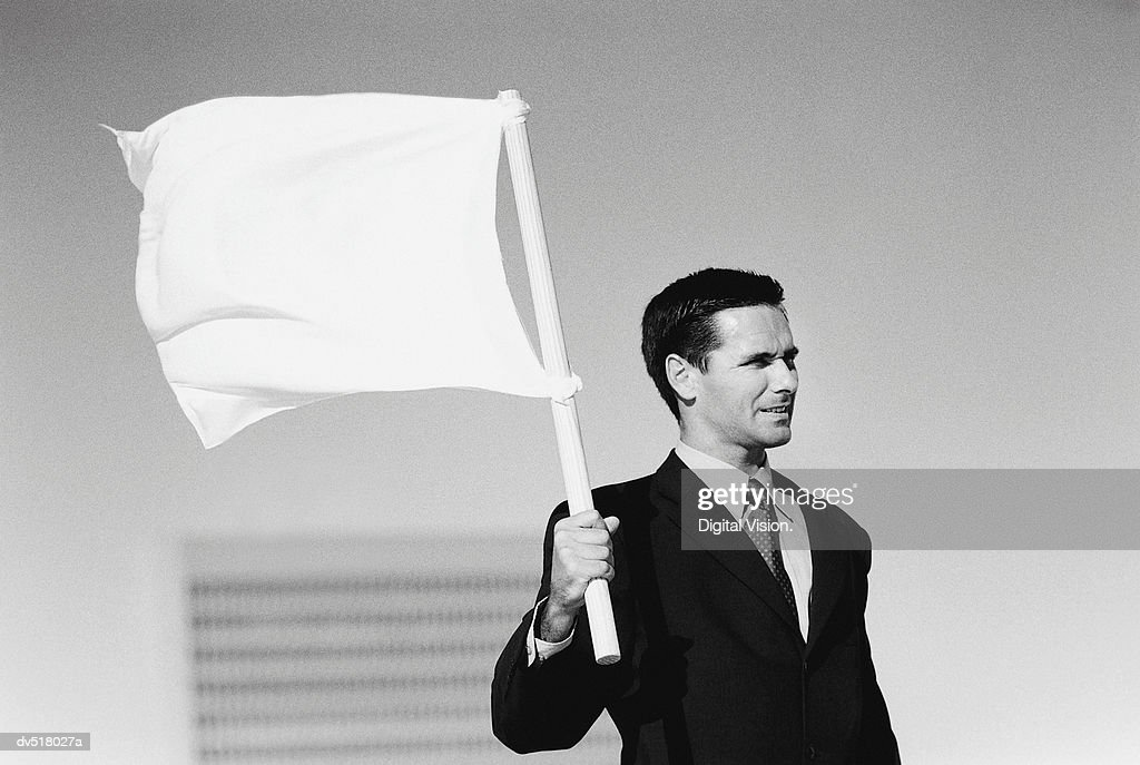 Businessman holding white flag : Stock Photo