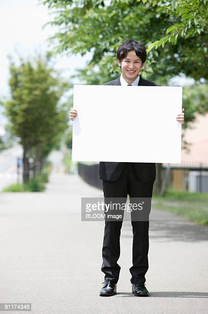 Businessman holding whiteboard