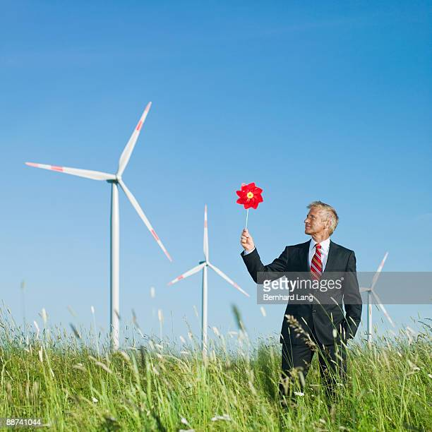 Businessman holding windmill