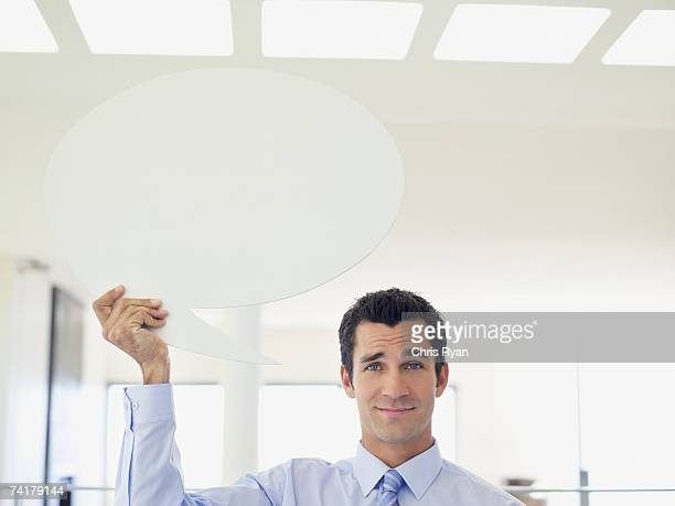 businessman holding word balloon - quotation text stock photos and pictures