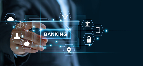 Businessman holding word banking in hand with icon network connection on virtual screen dark background 1023248390