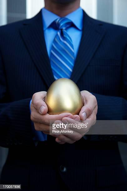 Geschäftsmann hält eine goldene Ei