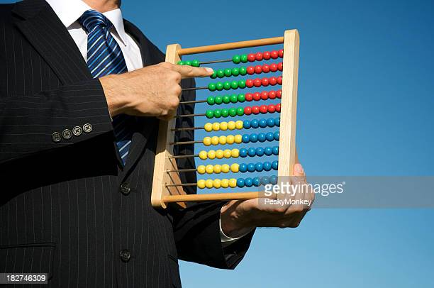 Businessman Holds Abacus in Blue Sky
