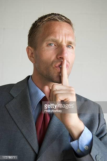 Businessman Holds Finger to Lips It's a Secret!