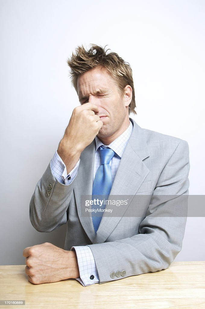 Businessman Holds His Nose Sitting at Desk : Stock Photo
