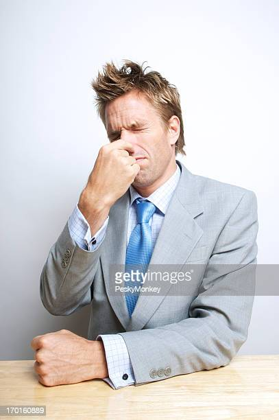 Businessman Holds His Nose Sitting at Desk