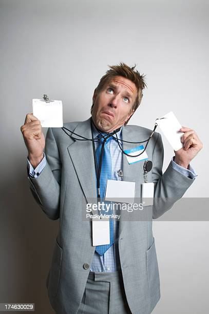 Businessman Holds Many Name Tags Looking Confused