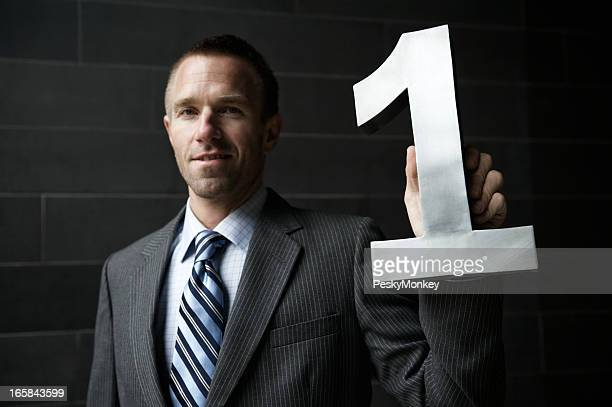 Businessman Holds Shiny Number One Dark Background