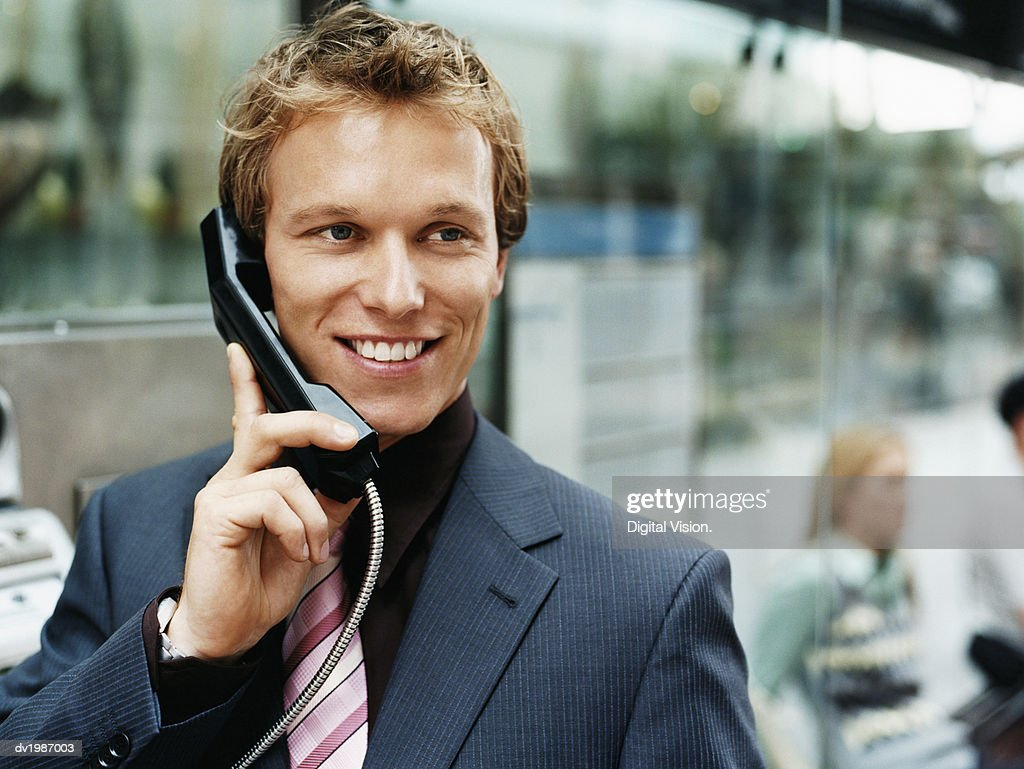 Businessman Holds the Telephone Receiver of a Payphone : Stock Photo