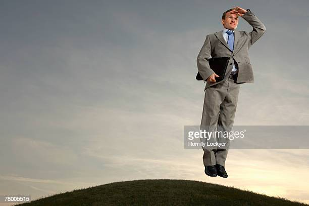 Businessman hovering above hill looking at horizon