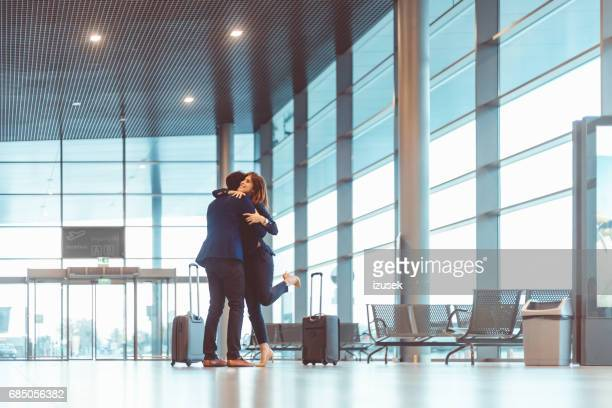 Businessman hugging a young woman at the airport terminal