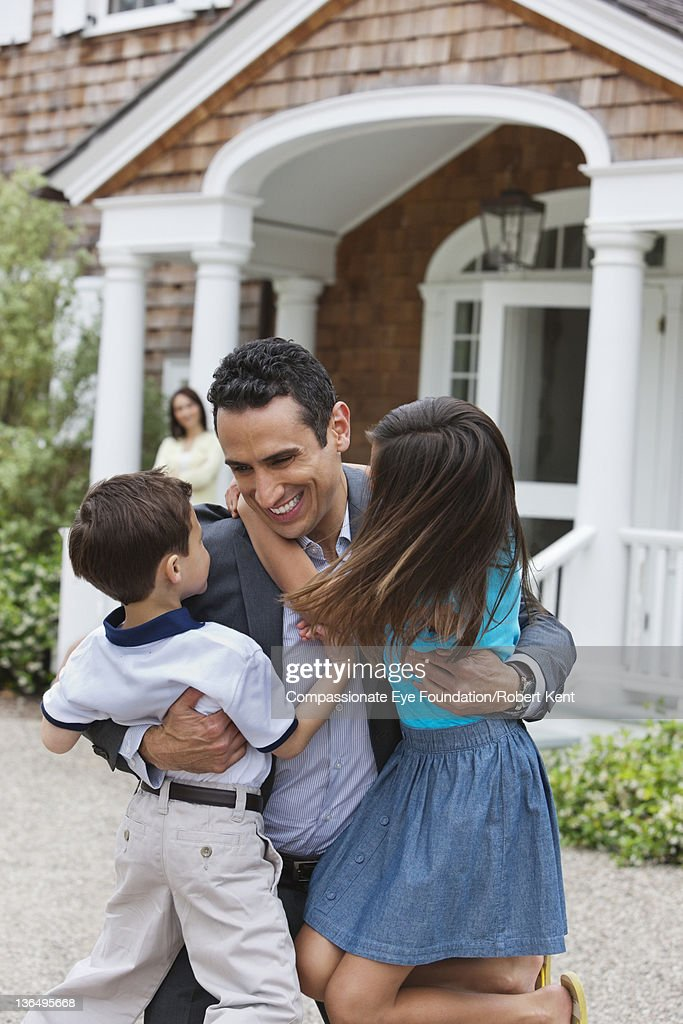 Businessman hugging children outside home : Stock Photo