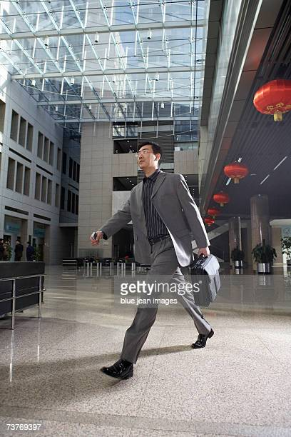 Businessman hurries through office lobby
