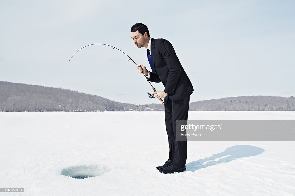 Businessman Ice Fishing on Frozen Lake. : Stock Photo