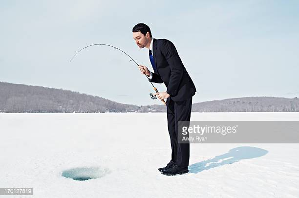 Businessman Ice Fishing on Frozen Lake.