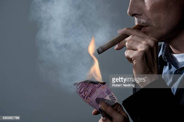 Businessman igniting a cigar with bank notes, Bavaria, Germany