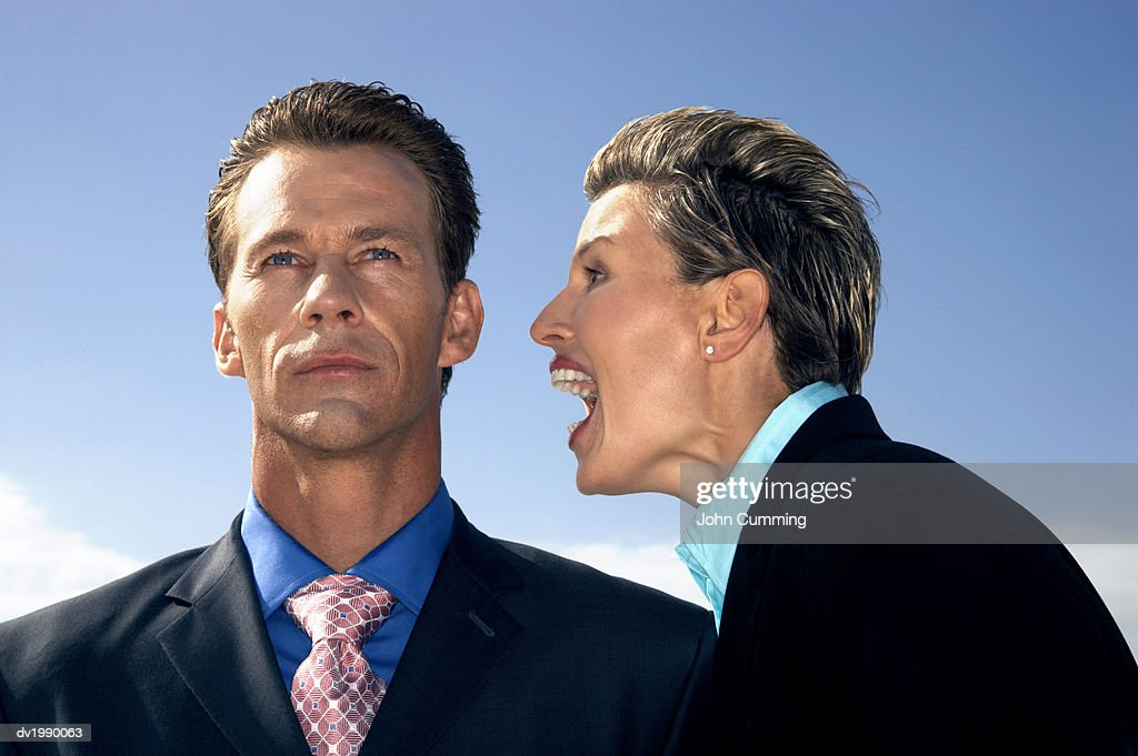Businessman Ignoring an Aggressive Businesswoman Shouting at Him : Stock Photo