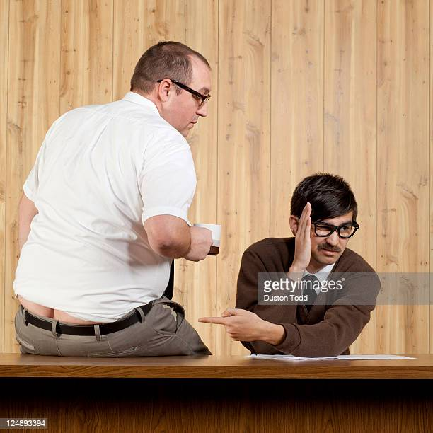 businessman ignoring colleague at desk in office - builders bum stock pictures, royalty-free photos & images