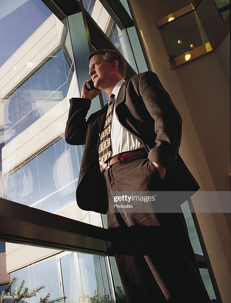 A businessman in a brown suit speaks on a cell phone while standing in front of a window of an office : Stockfoto