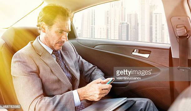 Businessman in a Cab Text Messaging