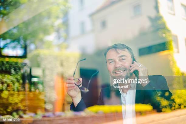 Businessman in a cafe behind windowpane