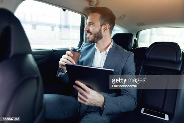 Homme d'affaires dans une voiture tenant la tablette numérique et souriant.