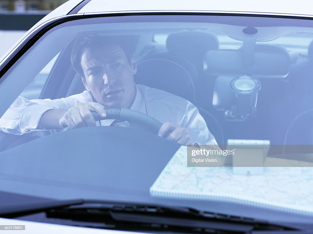 Businessman in a Car Looking Through His Car Windshield : Stock Photo