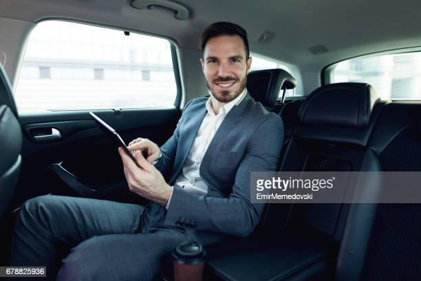 Homme d'affaires dans une voiture à l'aide de tablette numérique et souriant.