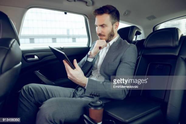 Homme d'affaires dans une voiture à l'aide de tablette numérique