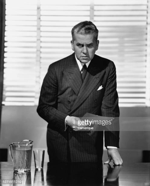 Businessman in a dark double-breasted pinstripe suit, leaning on the desk in front of him with his left arm, his right hand holding paperwork as he...