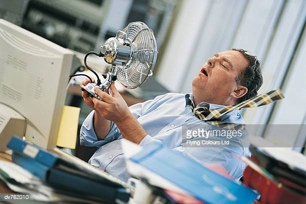 businessman in a hot office holding an electric fan to himself - calore concetto foto e immagini stock