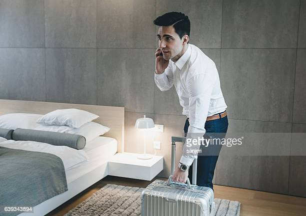 Businessman in a Hotel Room Talking on The phone