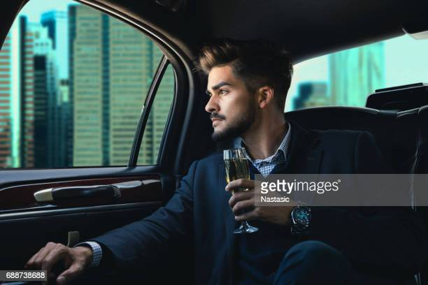 businessman in a limousine with champagne - vehicle interior stock pictures, royalty-free photos & images