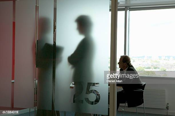 Businessman in a Meeting and Silhouettes of Businesswomen Talking Behind Frosted Glass