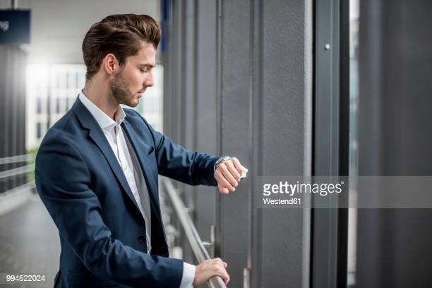 businessman in a passageway checking the time - armbanduhr stock-fotos und bilder