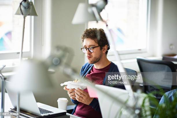 Businessman in a start-up office eating breakfast at his workstation